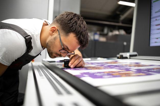 Travailleur vérifiant la qualité d'impression des graphiques dans une imprimerie moderne.