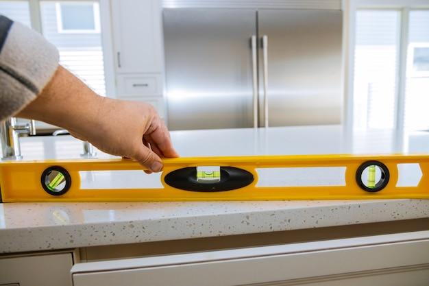 Un travailleur vérifie le nivellement des comptoirs en granit dans une rénovation de cuisine à domicile