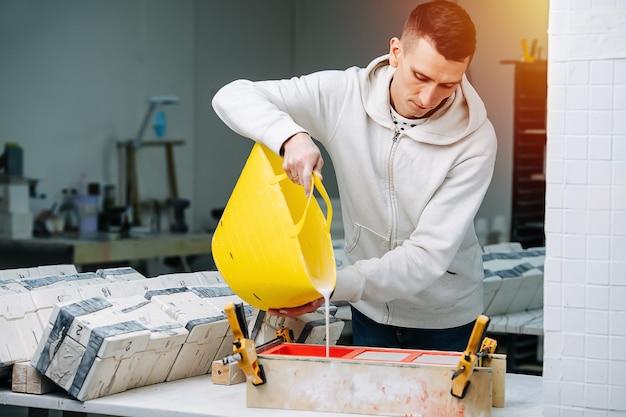 Travailleur versant du plâtre de gypse sous forme ouverte pour le moulage de moules pour faire de la vaisselle sur une table à partir d'un panier en plastique souple