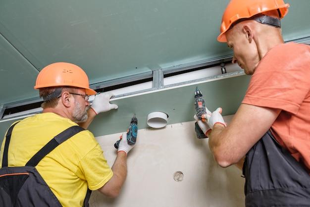 Les travailleurs assemblent la plaque de plâtre avec un trou d'aération