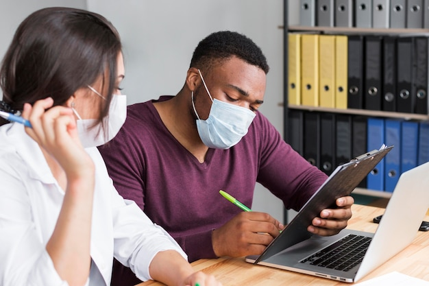 Travailleurs au bureau pendant la pandémie portant des masques médicaux
