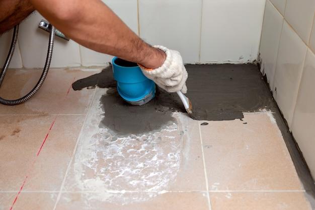 Les travailleurs de la construction brossent le ciment d'imperméabilisation sur les sols carrelés de la salle de bain.