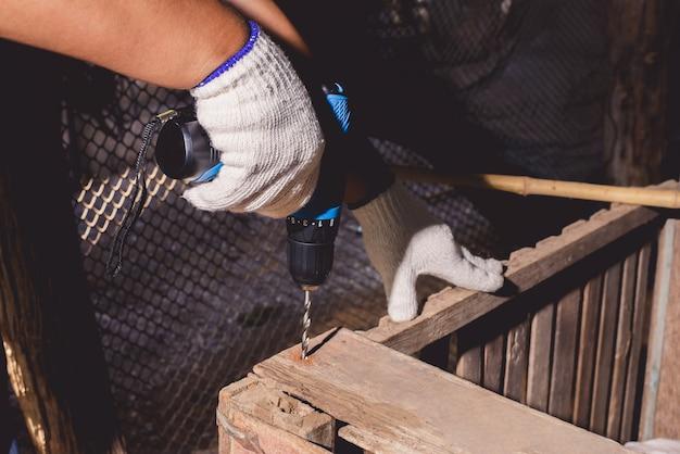 Travailleurs de la construction en chemise bleue avec des gants de protection et travaillant avec une perceuse électrique