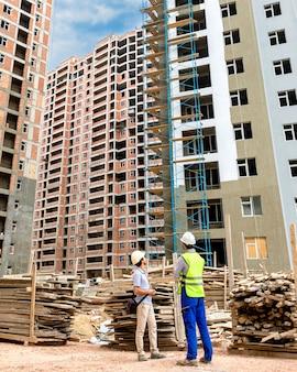 Travailleurs de la construction debout devant le bâtiment élevé