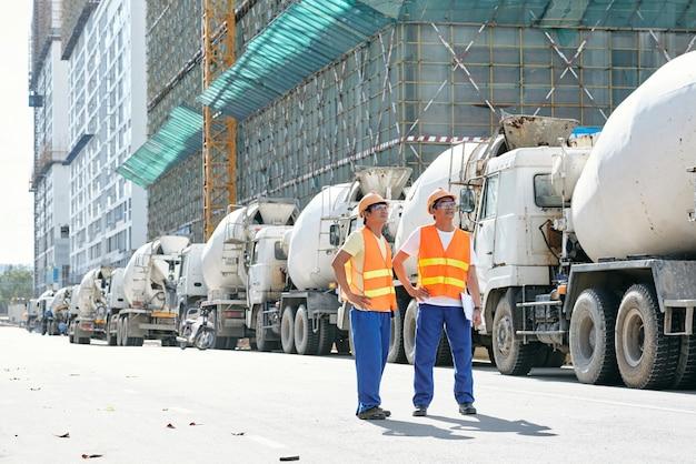 Travailleurs de la construction debout devant des camions malaxeurs garés et regardant le bâtiment dont ils ont besoin ...