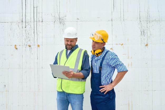 Travailleurs de la construction discutant du bâtiment