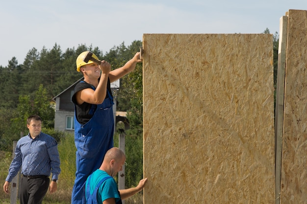 Travailleurs de la construction érigeant des murs préfabriqués en bois isolé positionnant un panneau pour l'installation
