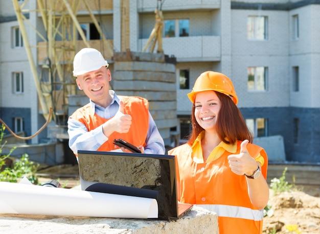 Travailleurs de la construction féminins et masculins de succès avec un ordinateur portable et des dessins