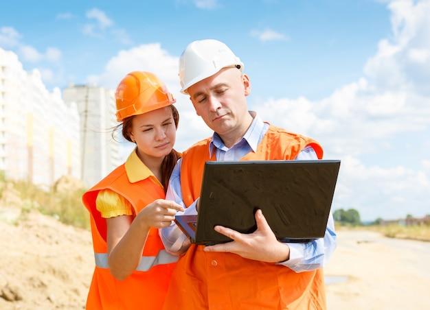 Travailleurs de la construction, femmes et hommes, regardant un ordinateur portable de maisons en construction
