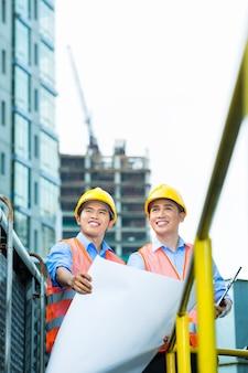 Travailleurs de la construction indonésiens asiatiques avec plan ou plan sur chantier