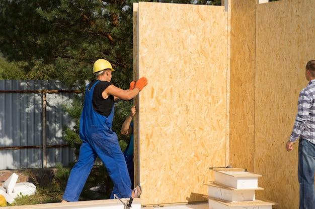 Travailleurs de la construction installant des murs préfabriqués en bois isolés dans le coin d'une nouvelle maison de construction sur un chantier