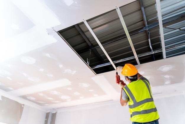 Les travailleurs de la construction installent la maison de plafond dans le bâtiment en construction, idées d'installation de plafond