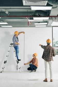 Travailleurs de la construction mesurant la longueur