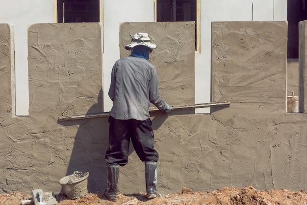 Travailleurs de la construction plâtrant un mur de bâtiment à l'aide de plâtre de ciment