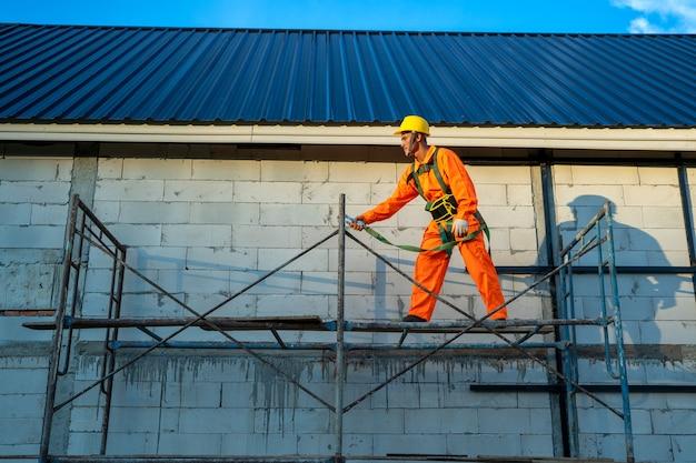 Travailleurs de la construction portant une ligne de sécurité pendant le travail sur le chantier de construction.
