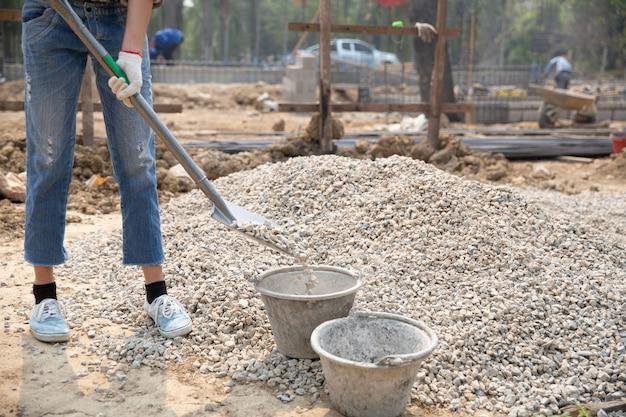 Travailleurs de la construction portant une pelle sur le chantier