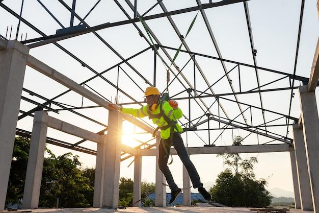 Les travailleurs de la construction tombent d'une hauteur mais ont la sécurité pour les aider. concept de prévention du danger des hauteurs avec sécurité sur le chantier.
