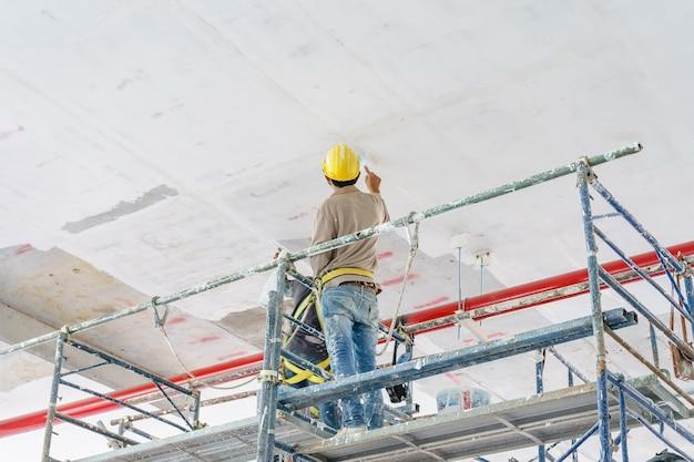 Travailleurs de la construction de la tour d'échafaudage peinture et rénovation de plancher du bâtiment