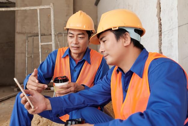 Travailleurs de la construction en uniforme et casques de protection discutant d'un nouveau mème sur les réseaux sociaux lorsqu'ils prennent un café ...