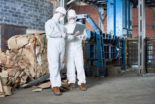Les travailleurs en costumes hazmat à l'usine de recyclage moderne