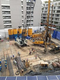 Travailleurs dans la zone de construction avec camion-grue et machine de maintien
