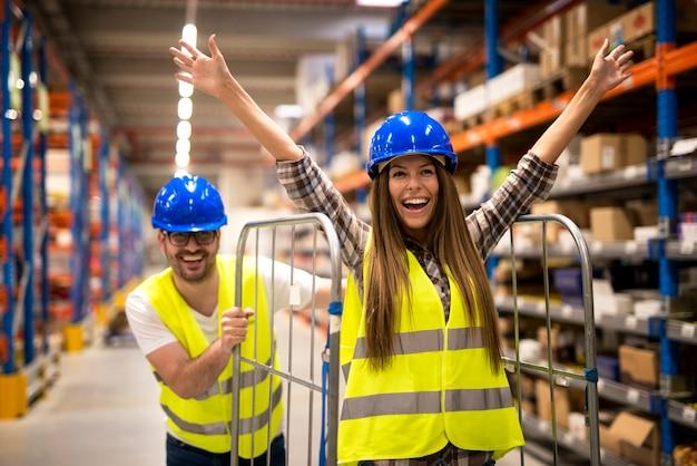 Les travailleurs d'entrepôt poussant des chariots et s'amusant au travail