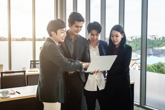 Travailleurs heureux qui réussissent un groupe d'hommes d'affaires asiatiques de divers genres (lgbt) voit un plan d'affaires réussi sur l'ordinateur portable dans la salle de réunion au bureau