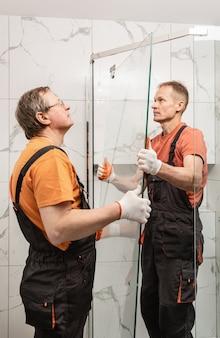Les travailleurs installent la porte vitrée de la cabine de douche.