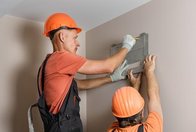 Les travailleurs installent un système divisé pour un système de climatisation domestique.