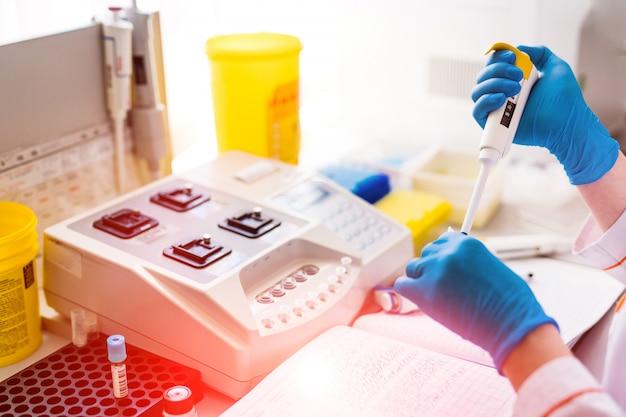 Les travailleurs de laboratoire professionnels verser des échantillons de sang dans des flacons sur la table.