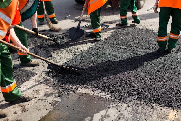 Les travailleurs sur la machine de finisseur d'asphalte pendant les travaux de réparation des rues de la route