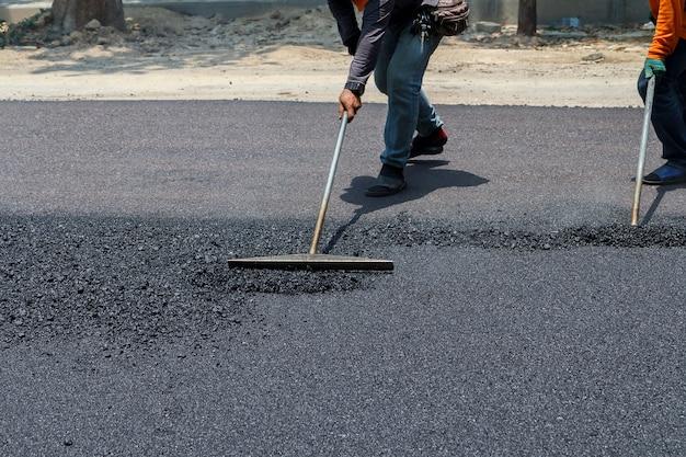 Travailleurs sur la machine à paver asphaltage pendant les travaux de réparation de rue road