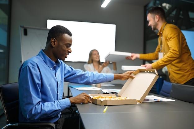 Les travailleurs mangent de la pizza, un déjeuner d'affaires au bureau informatique