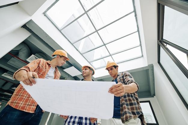 Travailleurs manuels avec plan de construction