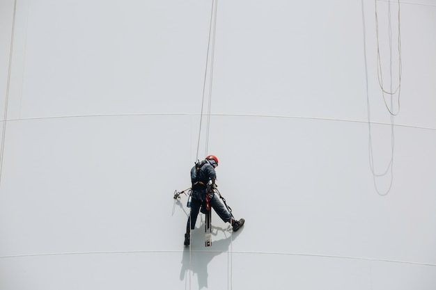 Les travailleurs masculins contrôlent la corde d'oscillation vers le bas l'inspection de l'accès à la corde du réservoir de l'épaisseur du pipeline et du gaz du réservoir