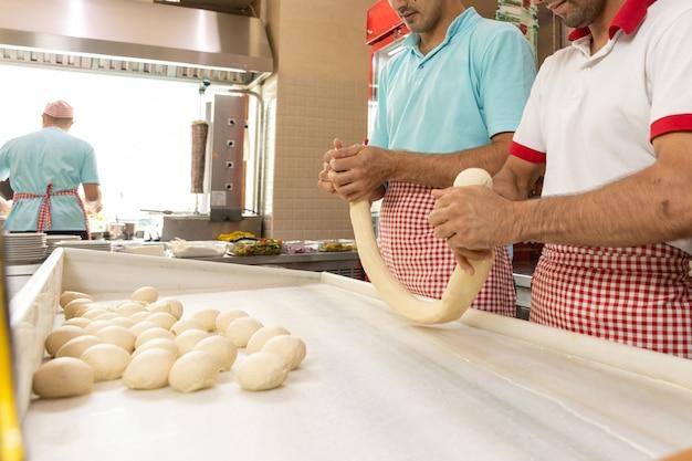 Les travailleurs masculins du restaurant découpent la pâte, la table et les mains dans la farine. cuisine de restaurant naturelle.