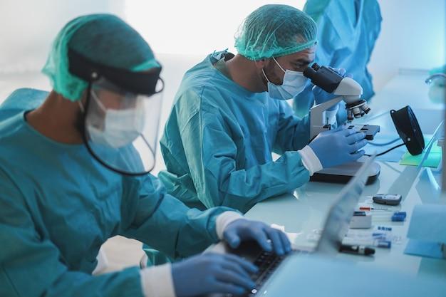 Les travailleurs médicaux en combinaison de matières dangereuses travaillant avec un ordinateur portable et un micoroscope à l'intérieur de l'hôpital de laboratoire pendant l'épidémie de coronavirus