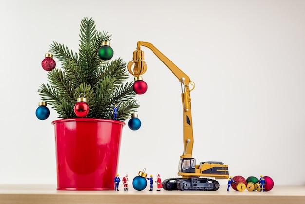 Travailleurs miniatures décorant l'arbre de noël.