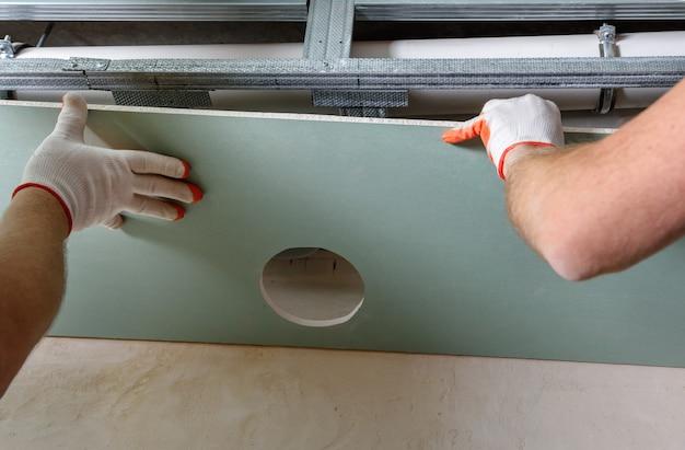 Les travailleurs montent une plaque de plâtre avec un trou d'aération