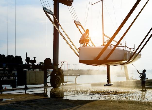 Les travailleurs nettoient les yachts avec des pistolets à eau au quai
