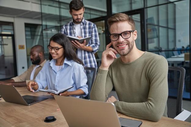 Travailleurs parlant ensemble dans une salle de conférence confortable