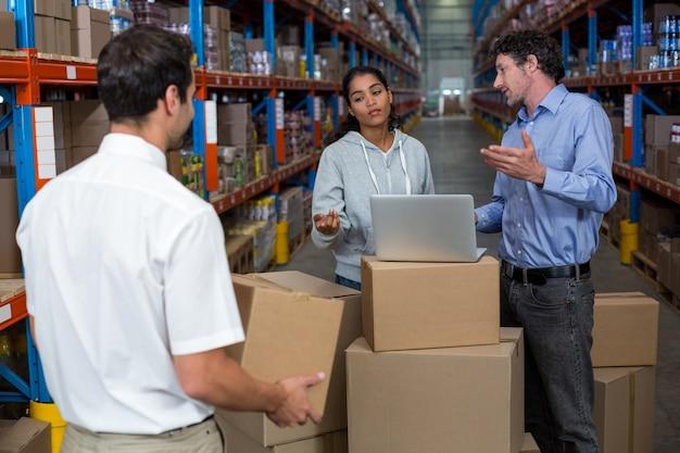Travailleurs parlant et travaillant avec un ordinateur portable mis sur du carton
