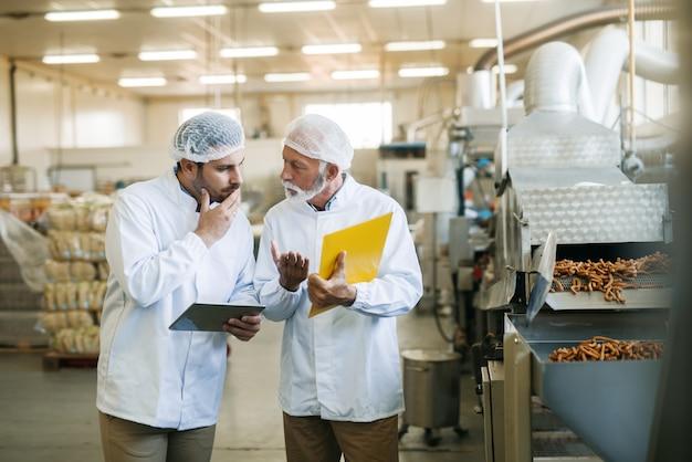 Les travailleurs parlent de la qualité des aliments. tableau des mains et tablette.