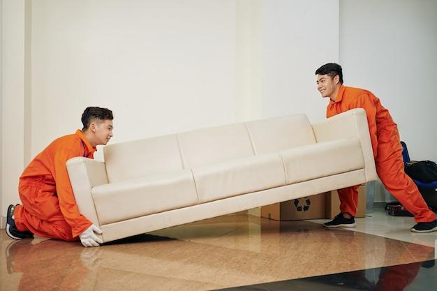 Travailleurs portant un canapé lourd