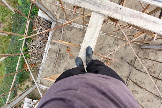 Les travailleurs portent des bottes sur des échafaudages en bois sur le chantier.