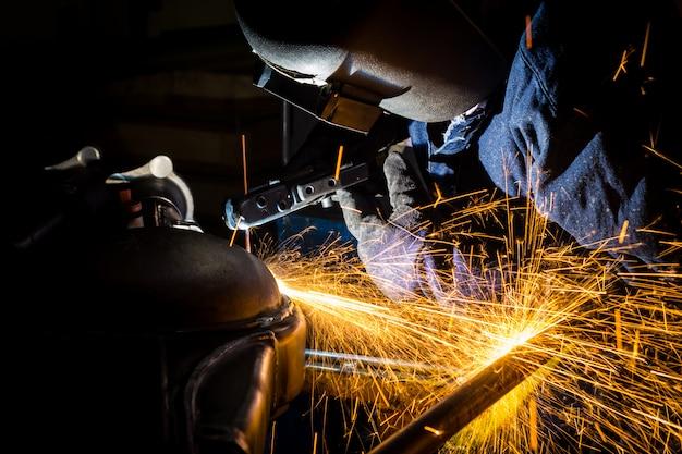 Les travailleurs rainurent avec des fils de soudure en carbone avec des étincelles