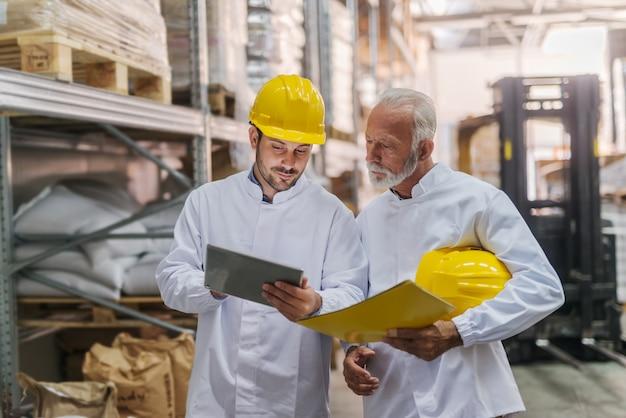Travailleurs à la recherche de tablette en entrepôt.