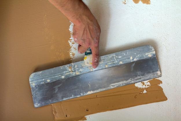 Les travailleurs de la rénovation à la main plâtrant le mur