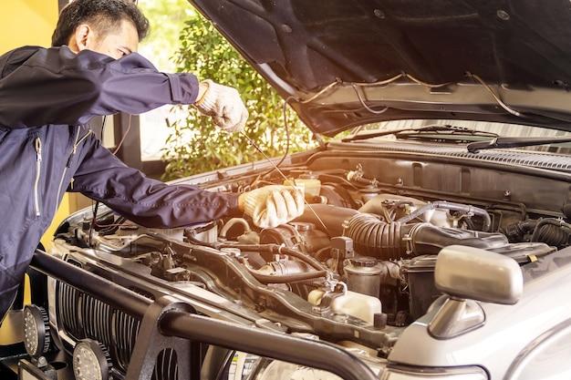 Les travailleurs de réparation automobile tirent la jauge de niveau d'huile de la voiture pour vérifier dans le centre de service de réparation de voiture