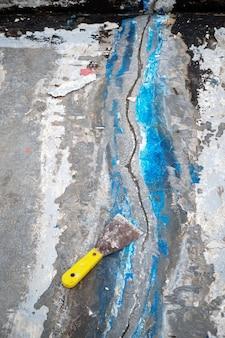 Les travailleurs réparent les fissures dans le sol en étalant le plâtre à l'aide d'une truelle réparer le pont d'imperméabilisation